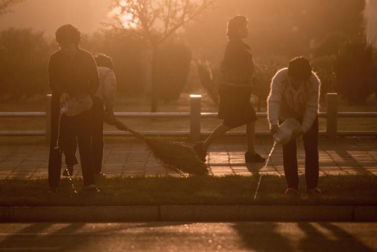 Three women clean and water a section of grass on a street of Pyongyang during sunrise. [Miguel Toran/Al Jazeera]