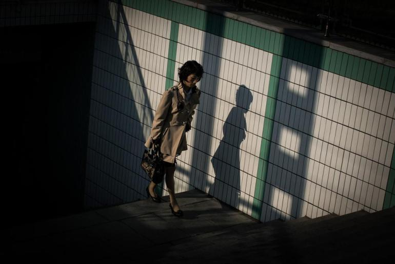 A woman comes out of a subway station in Pyongyang, North Korea. [Miguel Toran/Al Jazeera]