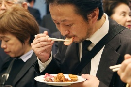 A supporter of Japan's whaling programme eats a slice of whale meat at a tasting event in Tokyo in April [AP]