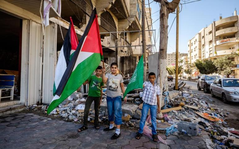 Hossam, Jihad and Fayyez proudly wave flags the day after the last ceasefire was announced.