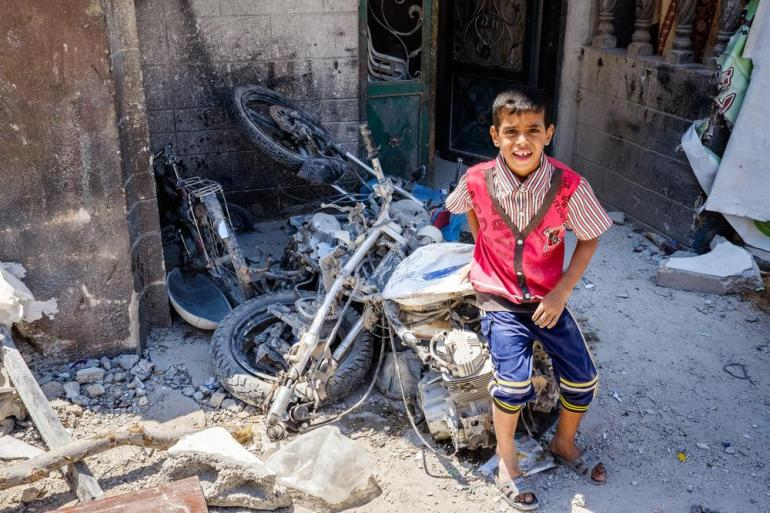 A child poses with his family(***)s motorcycle, which was destroyed along with their home in an Israeli air strike on a residential area in Rafah.