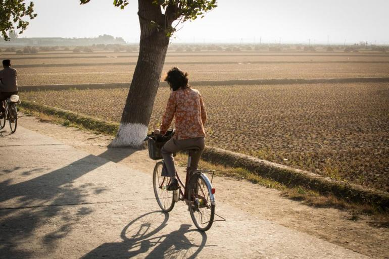 A woman rides her bicycle on a rural road in central North Korea.