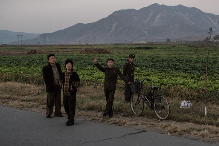 North Koreans stand next to a cabbage field.