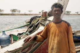 Squatter fishermen such as Benjol are threatened by sinking ground and rising Jakarta waters