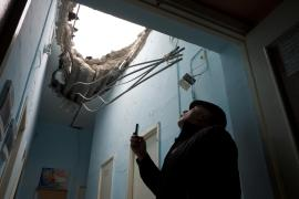 <p>A staff member at School 61 in Donetsk checks the damaged roof hours after it was hit by artillery fire, reportedly by the Ukrainian National Guard, during fighting for the control of the city(***)s airport.</p>