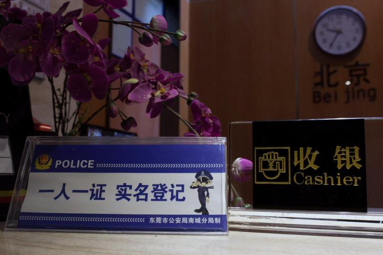The reception desk at one of the hotels in Dongguan with a sign reading: (***)One person, one document. Real name registration.(***) After the crackdown, many hotels have a strict policy of who can stay.