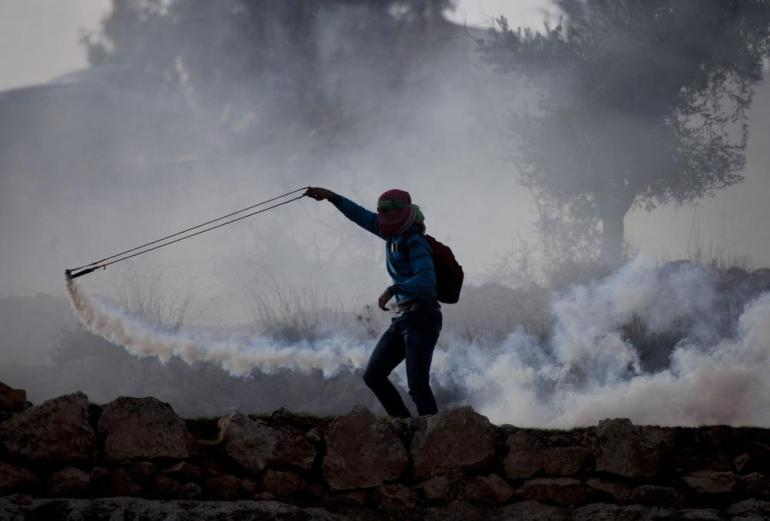 A Palestinian uses a slingshot to throw back a teargas canister that was fired by Israeli troops.