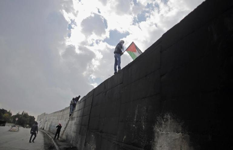 A protester holds a Palestinian flag as he climbs a section of Israel(***)s controversial barrier that separates the West Bank town of Abu Dis from Jerusalem. A Palestinian bus driver was found hanged inside his vehicle on Monday, an incident Israeli police described as a suicide. The driver(***)s family said he was killed by Israeli settlers.
