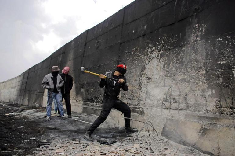 A Palestinian protester tries to hammer a hole through Israel(***)s controversial barrier that separates the West Bank town of Abu Dis from Jerusalem.