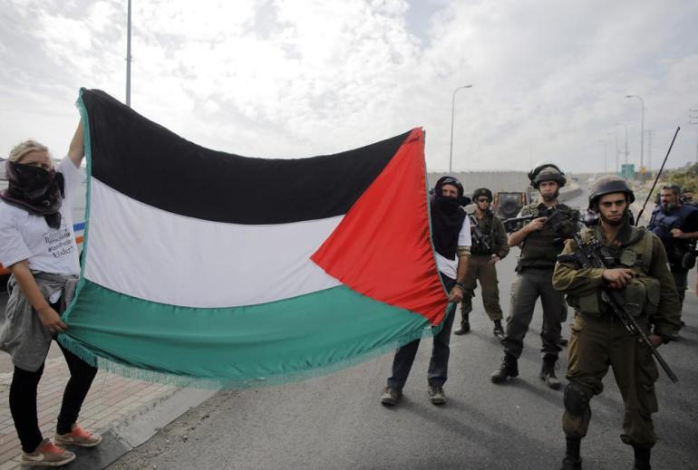 Foreign activists hold a Palestinian flag next to Israeli soldiers and border police during a protest against rising tensions in Jerusalem at a checkpoint near the West Bank village of Hizma, southeast of Ramallah.