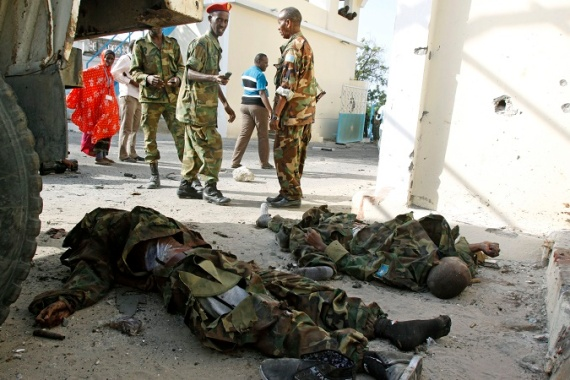 Somali soldiers look at the bodies of al-Shabab fighters near the presidential palace in Mogadishu in July [AP]