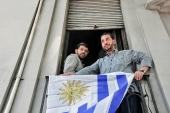 Two former prisoners at Guantanamo Bay stand on a balcony decorated with Uruguay's flag in Montevideo [AP]