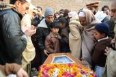 Pakistani mourners gather around a coffin during the funeral for a victim of an attack by Taliban militants [AFP]