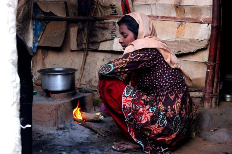A woman prepares a meal outside her shelter in a refugee camp in Jammu city.