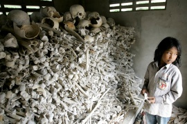 Meo Soknen, 13, stands inside a small shrine full of human bones and skulls, all victims of the Khmer Rouge [AP]