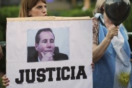 A woman holds a sign that reads 'justice' and an image of prosecutor Alberto Nisman [REUTERS]