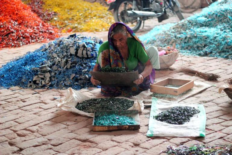 A worker collecting broken bangles to be recicled.