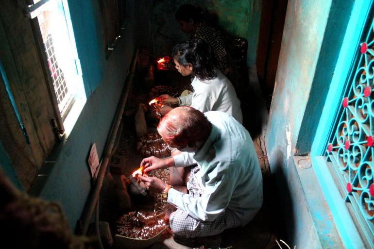Suresh Chani, 50, and his two daughters working in their congested workshop at home. Most of these workshops are indoors resulting in hazardous work place.