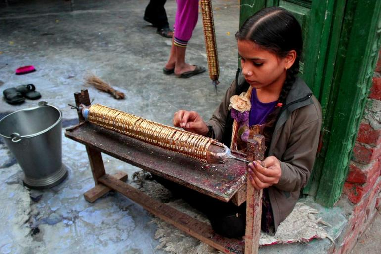 Mansi, 12 working on beautification of a set of bangles. Children are engaged into the trade by their families at an early age.