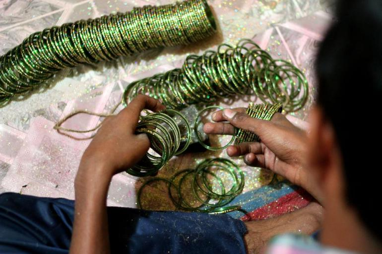 A worker checking each bangle by mildly striking on a stone. He identifies the damaged bagel with a distinct sound. On an average a worker earns 60 rupees (1 dollar) for striking 16000 bangles.