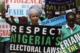 Members of the Nigerians United for Democracy Movement hold signs during a rally to protest against any further election postponement in Abuja on February 14 [REUTERS]