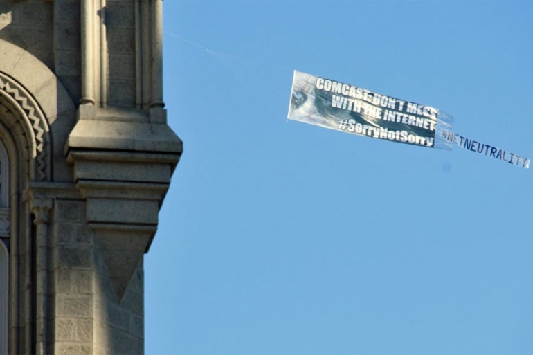 A banner flown over the corporate headquarters of Comcast [Al Jazeera]