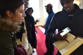 A Muslim man explains the Quran to visitors during an open day at a mosque in London [AFP]