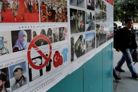 Anti-terrorism posters are pasted along the streets of Urumqi, in China's Xinjiang region [Getty Images]