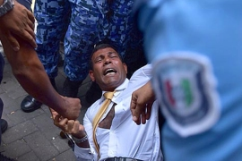 Nasheed fell to the ground after police pushed him in attempts to stop him from speaking to journalists [AFP]