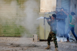 Libyan military soldiers fire their weapons during clashes with Islamic militias in Benghazi [AP]