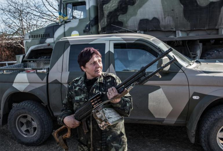 Nika, a female member of the Donbas battalion, unloads a machine gun from a truck at a military base in Berdianskwe. Female fighters are present in most of Ukraine's volunteer battalions.
