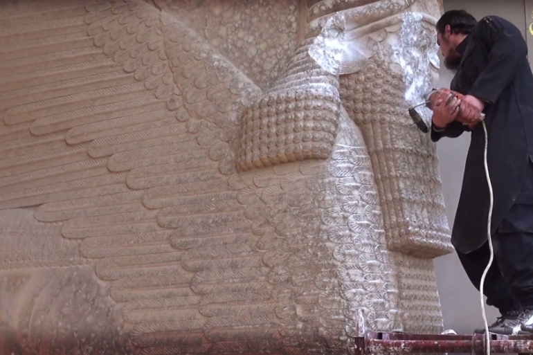 An ISIL fighter uses a power tool to destroy an Assyrian winged bull at a museum in Mosul, Iraq [AP]