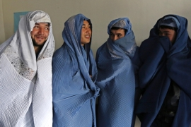 Male Afghan women's rights activists pose for media as they wear burqas to show their solidarity with Afghan women [REUTERS]