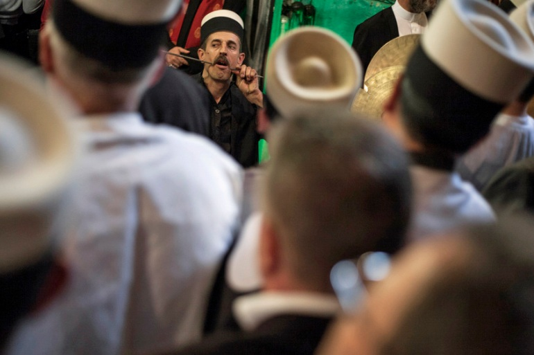 A member of the Sufi sect pierces himself with a zarf during the Nowruz ritual [Ferdi Limani/Al Jazeera]