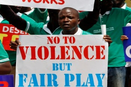 Members of Nigerians United for Democracy Movement hold signs during a rally in Abuja in February [Reuters]