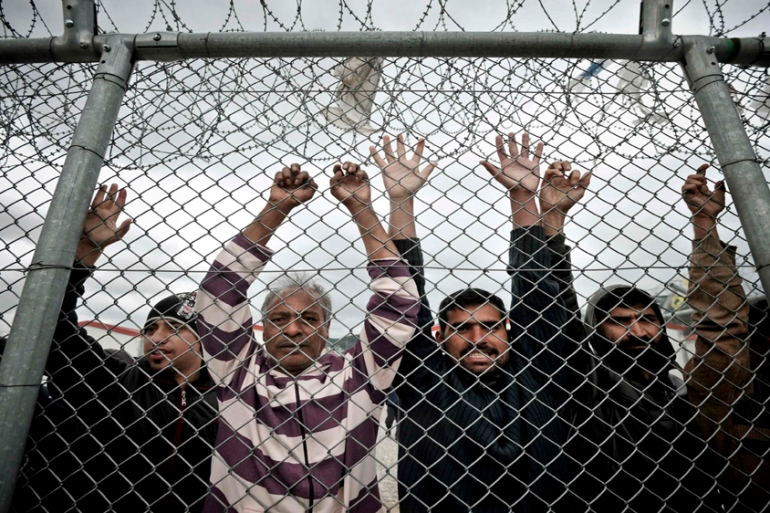 Immigrants stand behind a fence at a detention centre in the Amygdaleza suburb of Athens [Reuters]