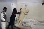 A man topples a statue in a museum said to be Mosul in this still image taken from an undated video [REUTERS]
