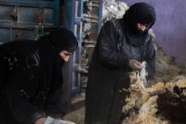 Iraqi women clean piles of animal wool in a tanning factory in the area of Nahrawan, southeast of Baghdad [AFP]