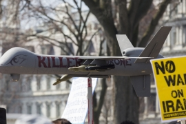 Protesters carry placards near a fake drone in front of the White House during an anti-war march in Washington, DC [AFP]
