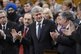 Harper is applauded after introducing a motion to expand and extend Canada's war against ISIL [AP]