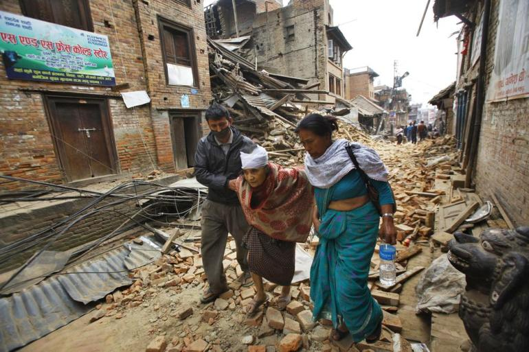 An injured elderly woman is taken to what was left of her home after treatment.