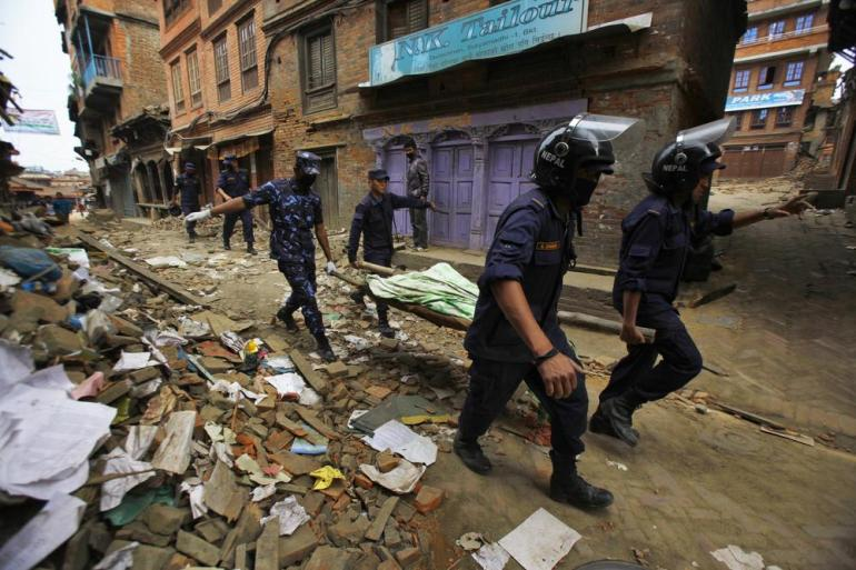 A Nepalese rescue team carries the body of a victim recovered from the debris of a building in Bhaktapur that collapsed after the earthquake.