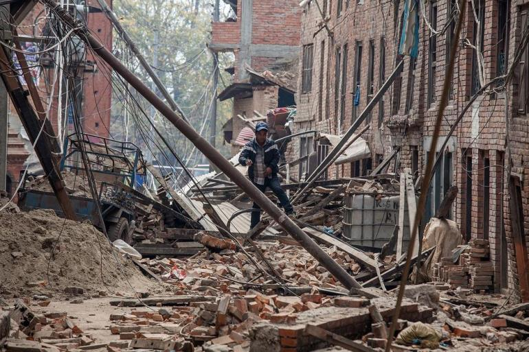 A man runs down a debris-covered street  after buildings collapsed in Bhaktapur, Nepal.