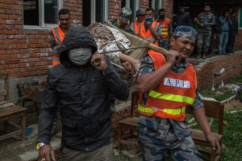 Emergency workers carry the body of a victim of the earthquake. Relief agencies have already warned that as many as six million people might be affected in Nepal by Saturday's disaster.