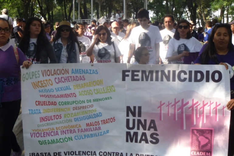 Protesters hold a sign up reading 'Not one more femicide' during a march in Guadalajara [Duncan Tucker/Al Jazeera]