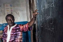 Sixth-grade teacher Andrew Kabia writes Ebola prevention messages on a blackboard [Tommy Trenchard/Al Jazeera]