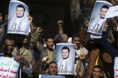 Yemeni men chant slogans while holding posters of Houthi rebel leader [AP]