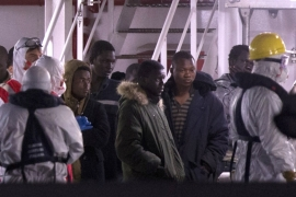 Survivors of the boat that overturned off the Libyan coast, wait to disembark from an Italian coastguard ship in Italy [AP]