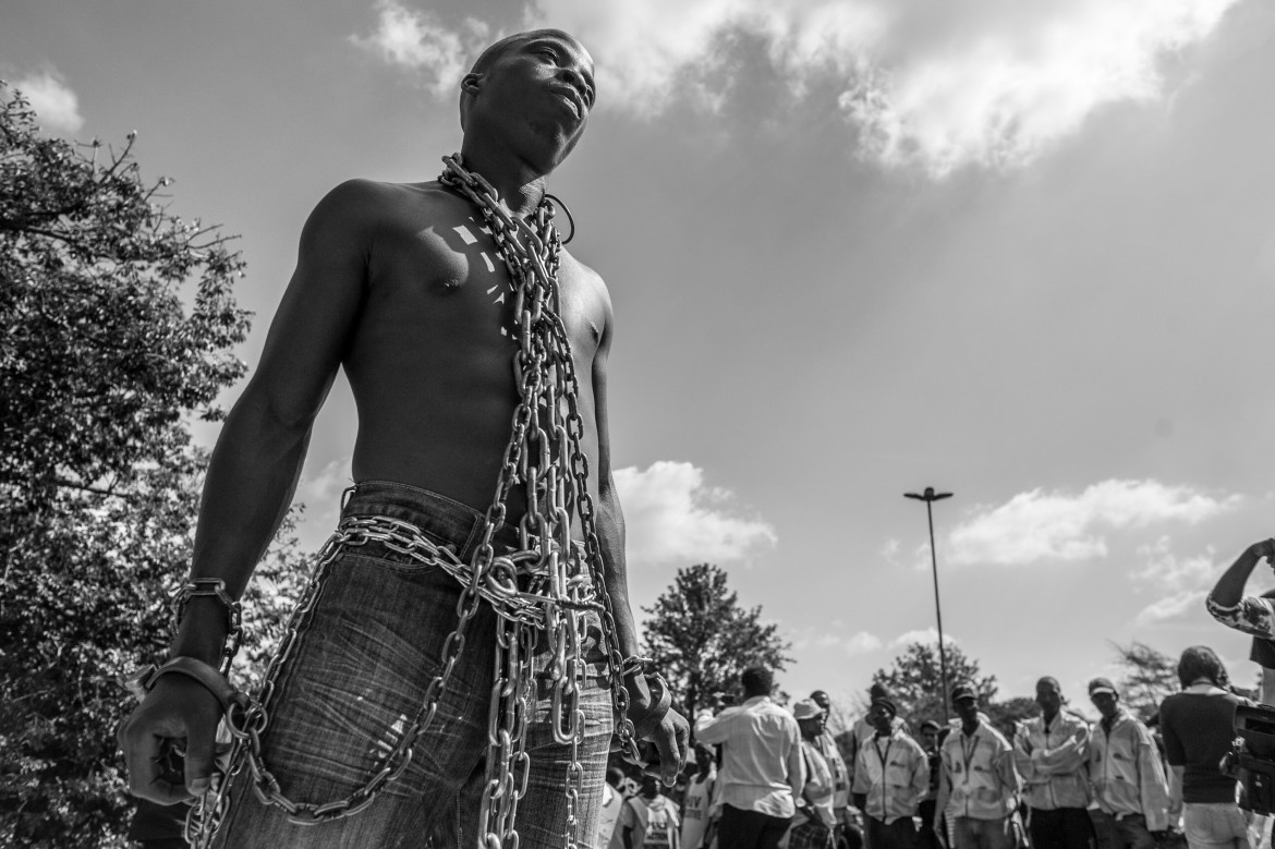 A protester attending an anti-xenophobia rally in Johannesburg is seen wrapped in chains as he joined thousands who marched through the city demanding an end to the violence. [Ihsaan Haffejee/Al Jazeera]