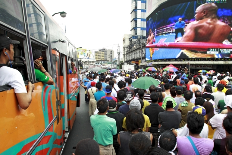 Fans watch the fight on a live telecast monitor along a busy street in Manila [REUTERS]